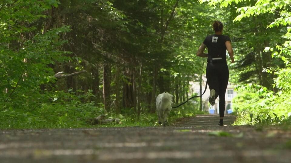 La jeune femme qui court avec son chien dans un bois.