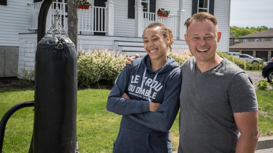 Les deux personnes dans la rue devant une maison et à côté d'un sac de boxe.
