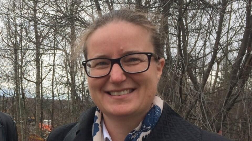 Une femme qui sourit dans un boisé.