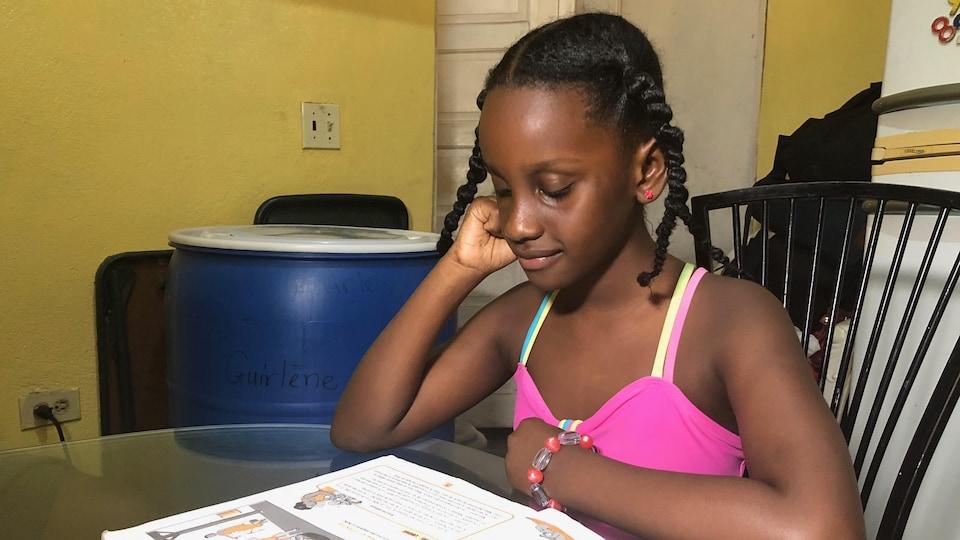 Une jeune fille lit un manuel scolaire.