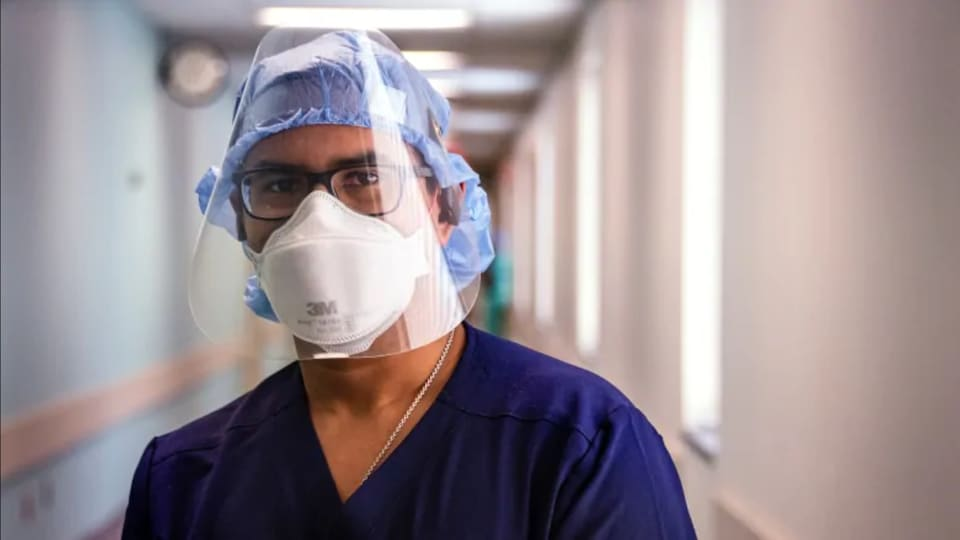Un médecin masqué dont le visage est entièrement protégé par une plaque de plexiglas.