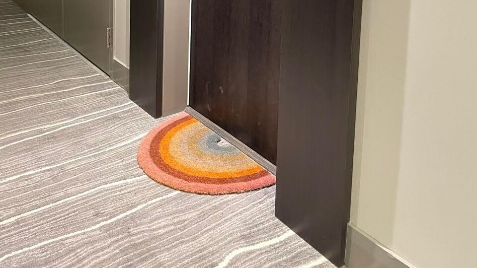 Un tapis d'entrée en forme d'arc-en-ciel.