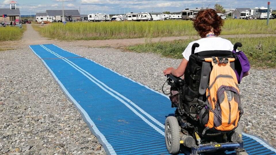 Une personne handicapée circule sur le tapis déroulé sur la plage
