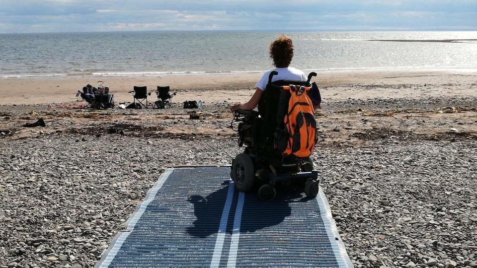 Une personne en fauteuil roulant est sur une plage grâce à un tapis au sol
