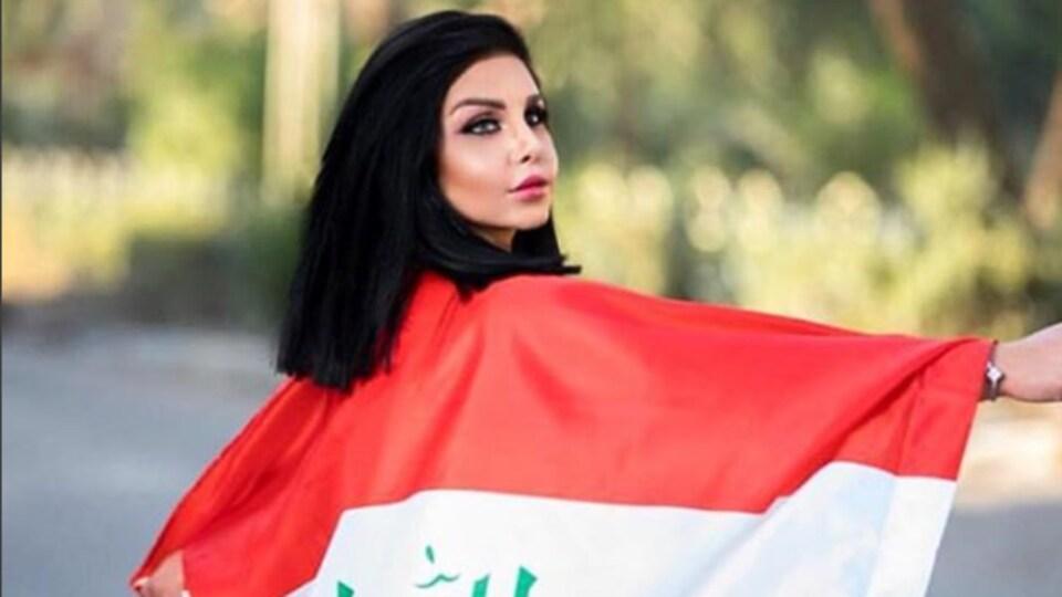 Tara Farès portant un drapeau de l'Irak.