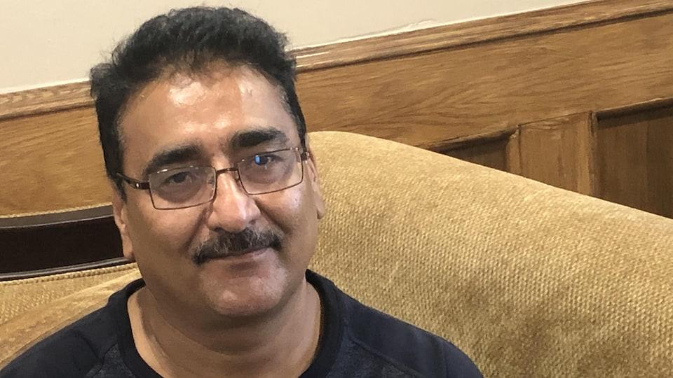 Tariq Chaudhry sourit timidement à la caméra, assis sur un fauteuil.