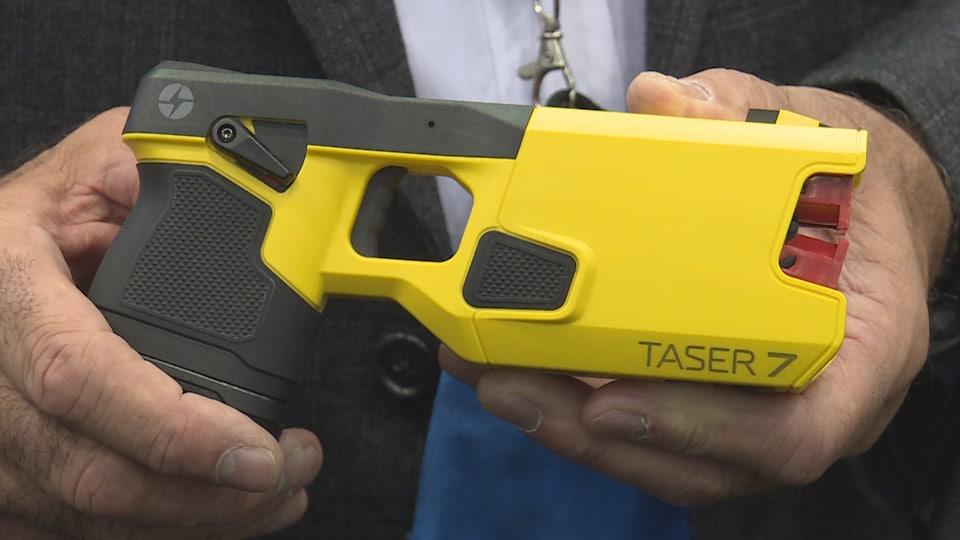 Plan serré de deux mains qui tiennent un pistolet électrique sur lequel il est écrit Taser 7.