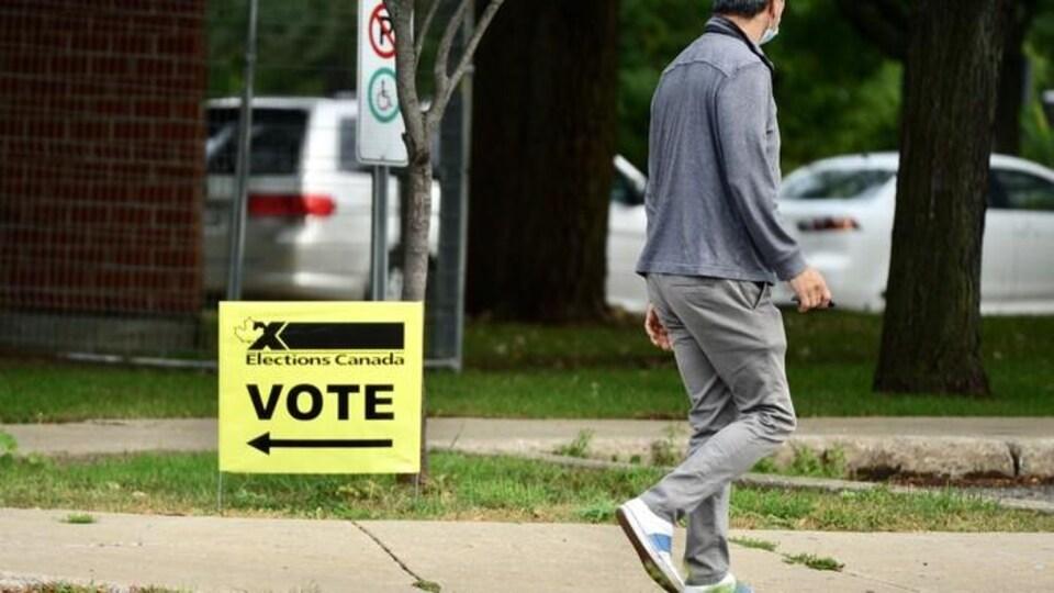 Un passant marche sur un trottoir. Dans le carré de pelouse à côté de lui est plantée une affiche sur laquelle est écrit : « Élections Canada Vote ».