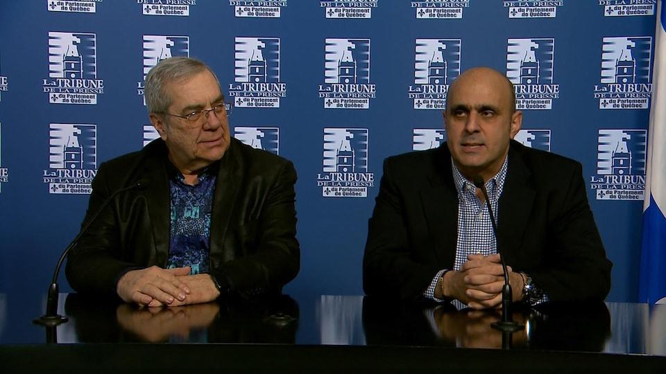 François Cyr et Abdallah Homsy, assis devant des micros, s'adressant aux journalistes.