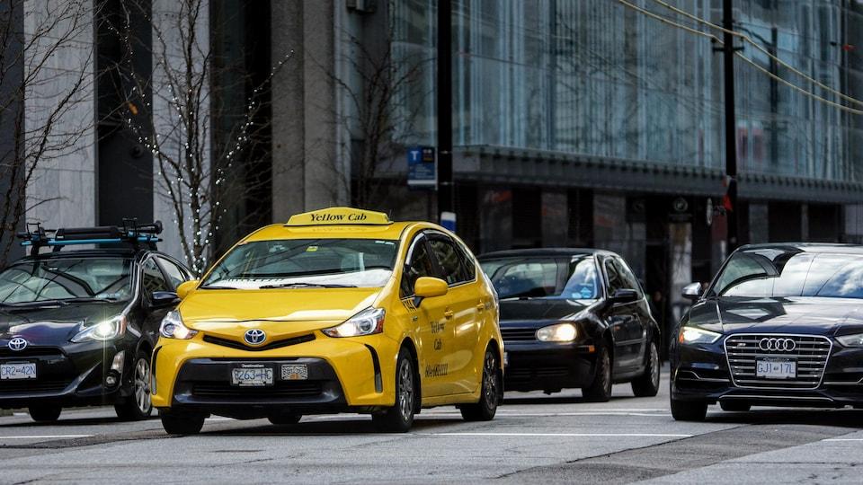 Un taxi jaune est dans une rue, entouré d'autres véhicules.