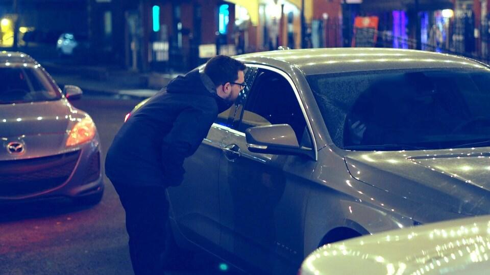 Un homme se penche près de la fenêtre côté passager d'une voiture la nuit.