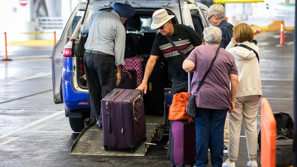 Des voyageurs empilent leurs valises dans un taxi à l'aéroport.