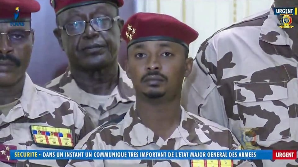 Un jeune homme en tenue militaire entouré d'autres militaires.