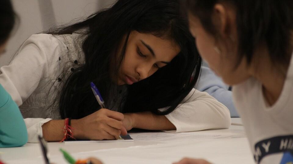 Une fille prend des notes sur un calepin à une table entourée d'autres jeunes.