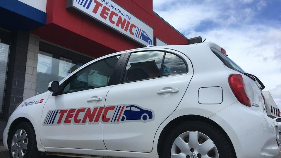 Une voiture Tecnic stationnée devant l'école de conduite.
