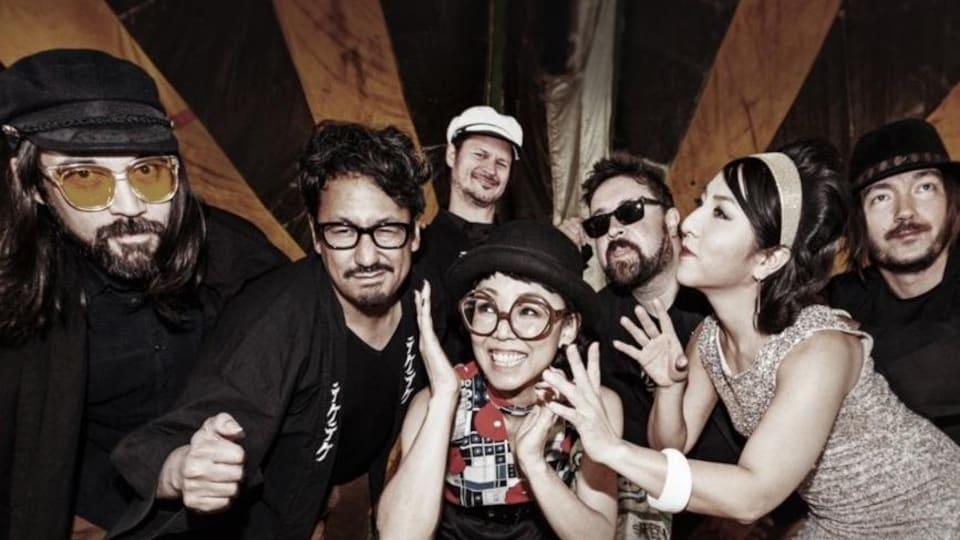Cinq musiciens et deux musiciennes posent pour une photo de groupe.