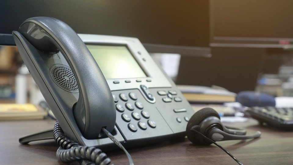 Une console téléphonique avec un casque d'écoute et deux écrans d'ordinateur.