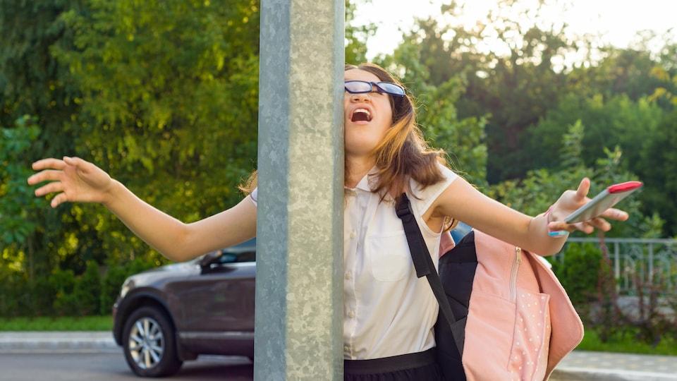 Une femme distraite par son téléphone cellulaire frappe un poteau en marchant.