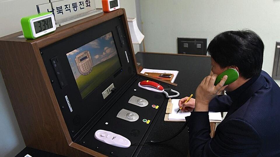 Un responsable sud-coréen parle dans un téléphone vert devant une table sur laquelle on voit un écran. La console devant lui contient également un téléphone rouge.