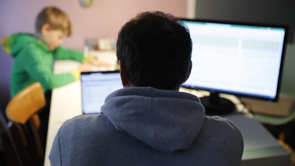 Une personne travaille à son ordinateur avec un enfant devant elle.