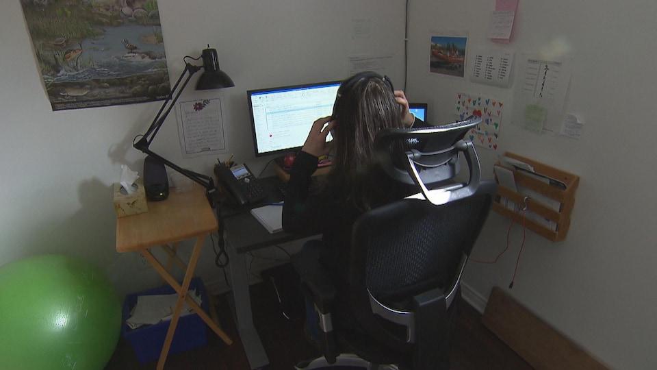 Une femme assise à un bureau d'ordinateur à la maison.