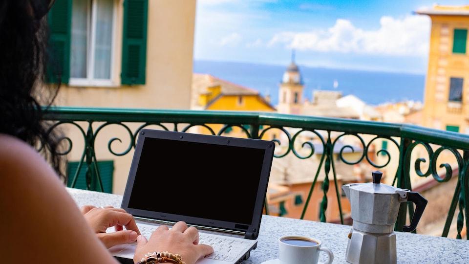 Une femme travaille sur son portable sur un balcon avec vue sur la mer et les toits de la ville.