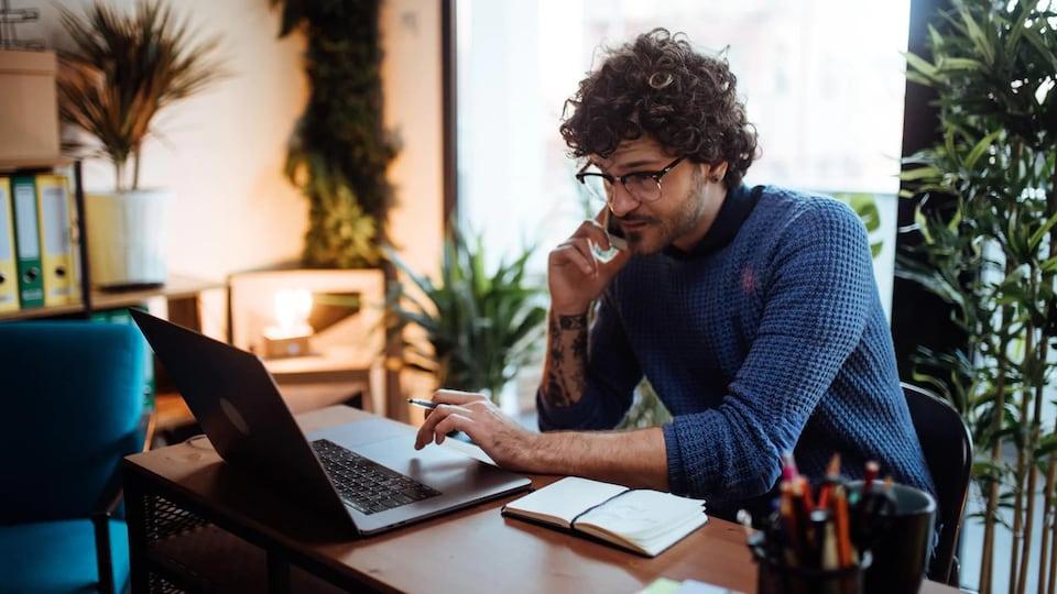 Un homme au téléphone devant son ordinateur.