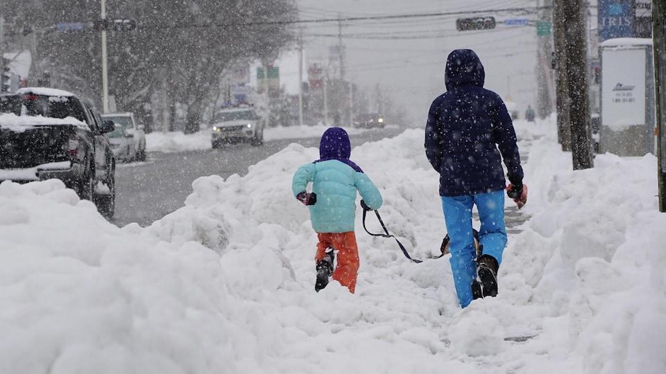 Un parent, un enfant et un chien marchent sur un trottoir enneigé de Rimouski.