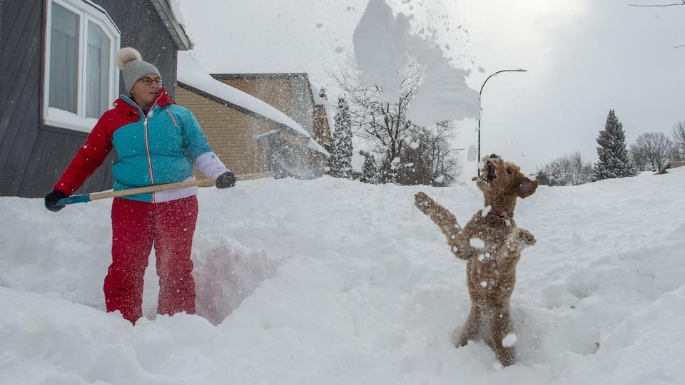 Rene Lanteigne, de Deux-Montagnes, dégage son entrée au grand bonheur de son chien.