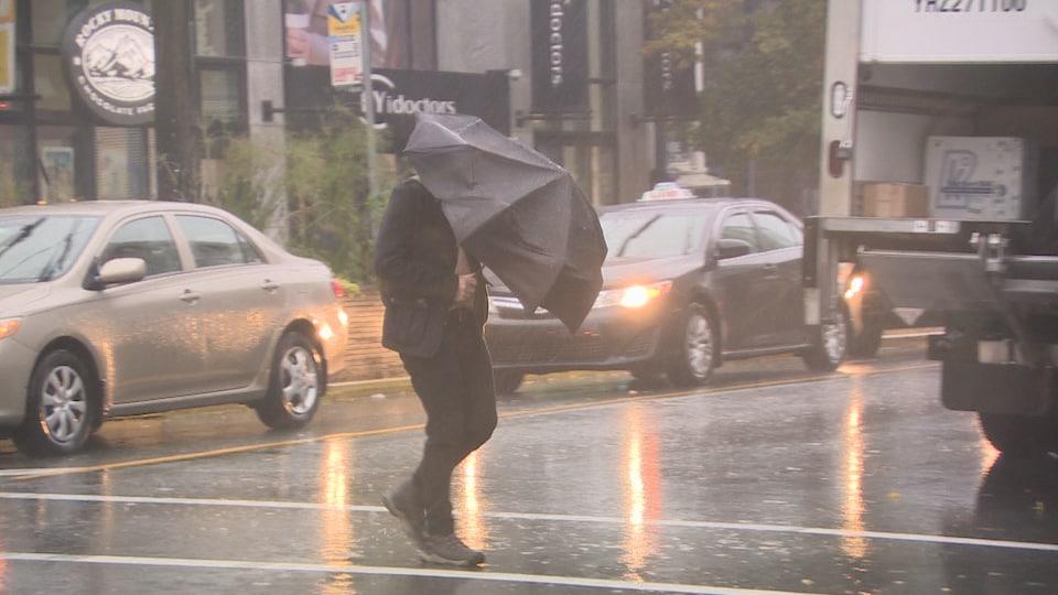 Un piéton traverse une rue, tenait à grand-peine son parapluie.