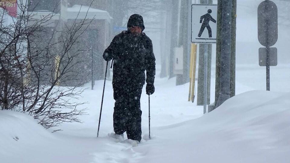 Un homme se déplace sur un trottoir enneigé en faisant du ski de fond