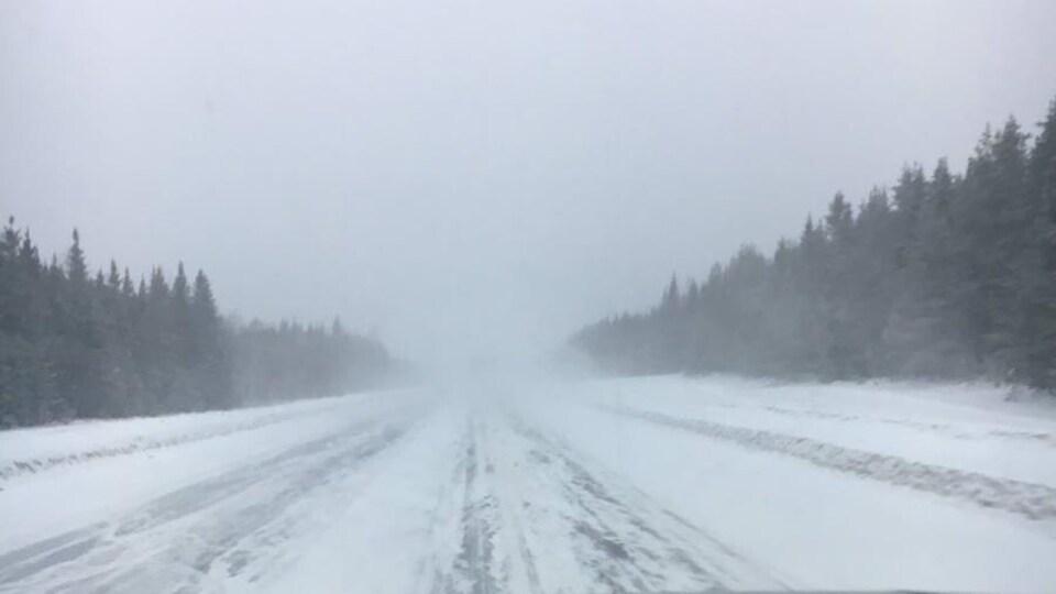 La route est enneigée et de la poudrerie réduit la visibilité.