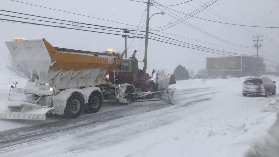 Une camion de déneigement circule sur la chaussée enneigée, derrière une voiture.