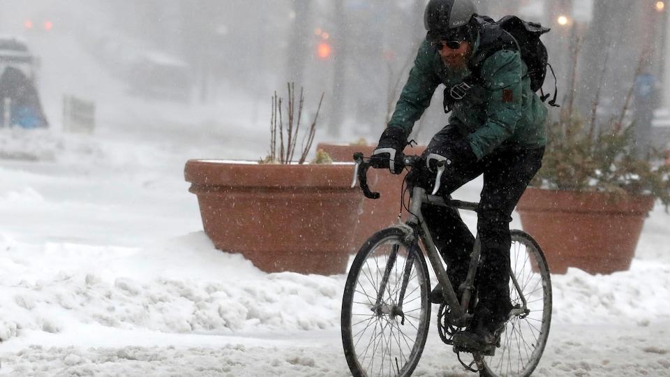 Un cycliste avance péniblement sur la chaussée couverte de neige, à Brooklyn, le 14 mars 2017.