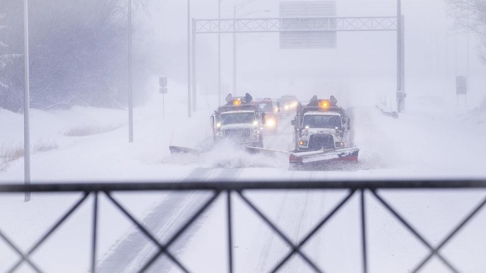 Des camions du ministère des Transports sur l'autoroute.