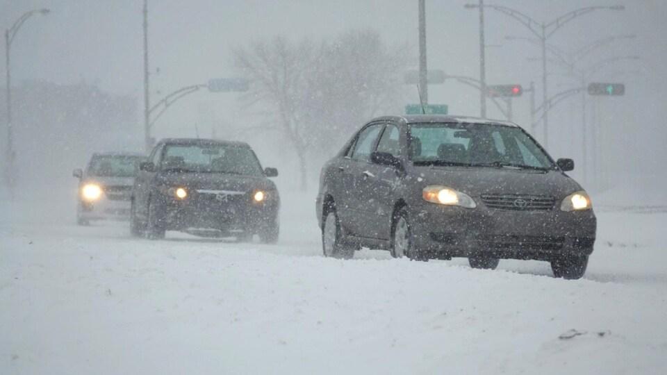 Des voitures circulent sur la route enneigée.