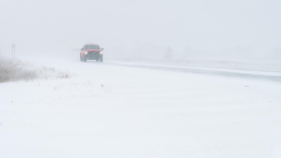 Un camion roule sur une route enneigée.