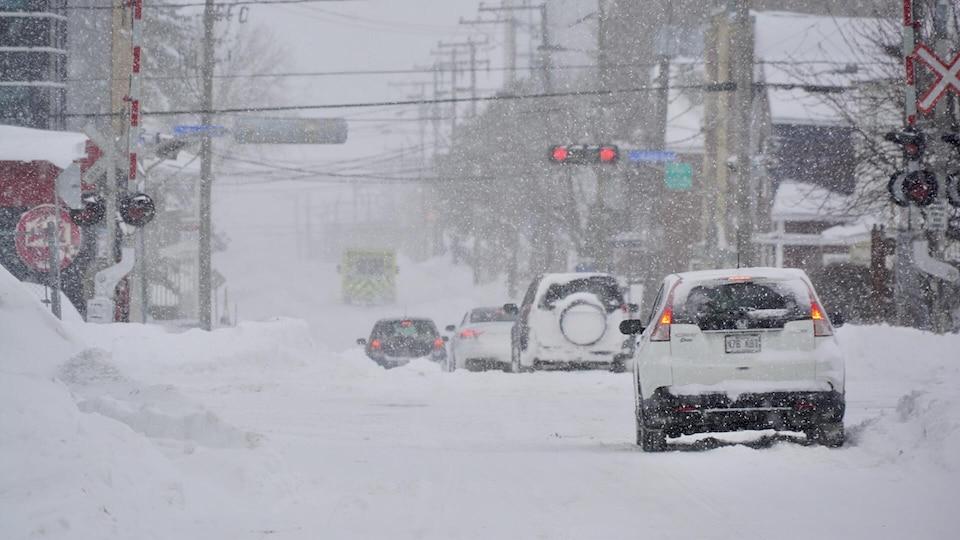 Des voitures circulent dans une rue enneigée.