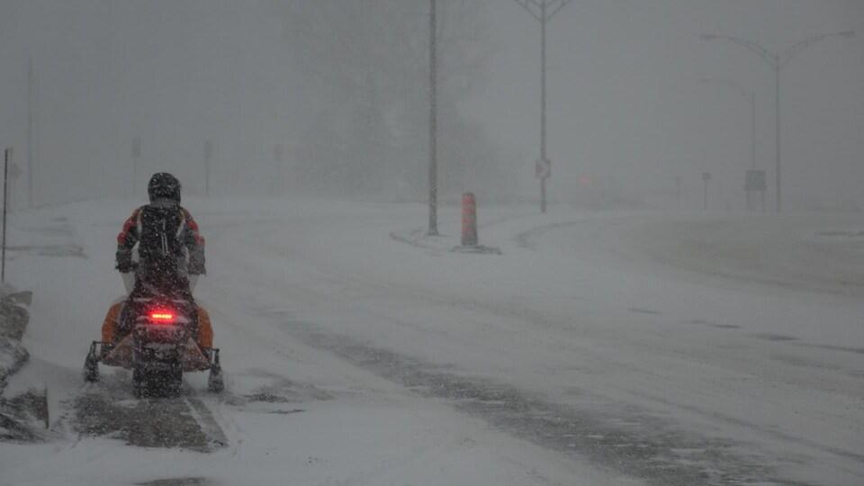 Un individu circule en motoneige sur un axe routier enneigé près de Rimouski.