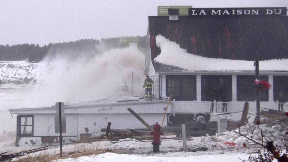 Une vague frappe la Maison du pêcheur.