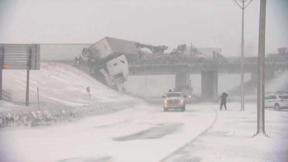 Un camion semi-remorque perché en haut d'un viaduc, il y a énormément de neige autour.