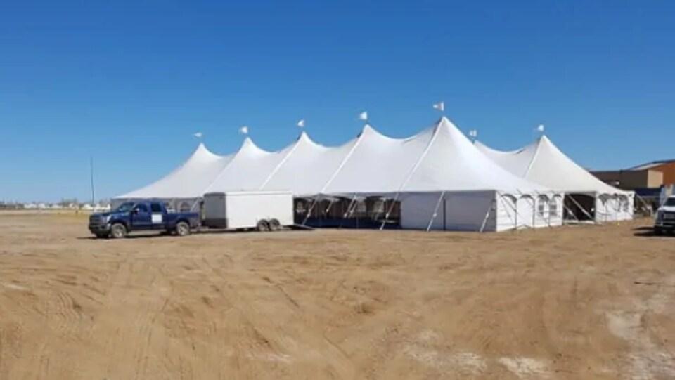 Un terrain vague sur lequel est installée une grande tente blanche.