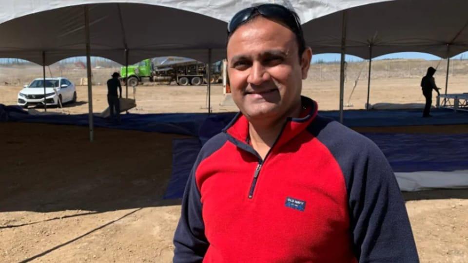 Un homme pose fièrement à la caméra. Derrière lui se trouve un terrain vague où une tente est installée. On voit aussi un camion.