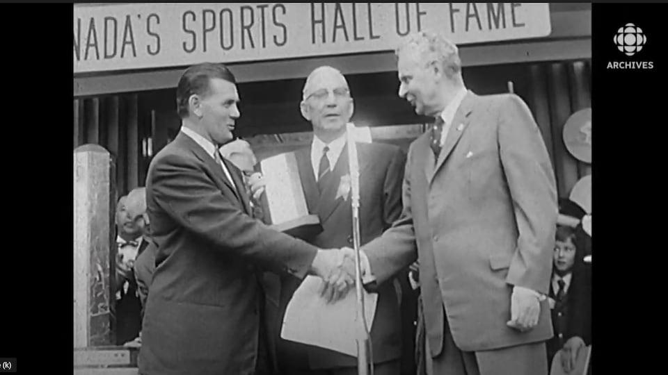 Deux homme se serrent la main sur une estrade, un autre homme au centre tient un trophée.
