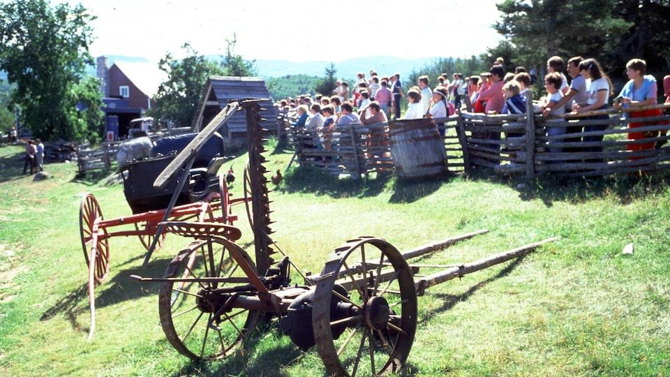 Foule de gens derrière une clôture dans Charlevoix avec machinerie agricole d'époque en avant-plan.