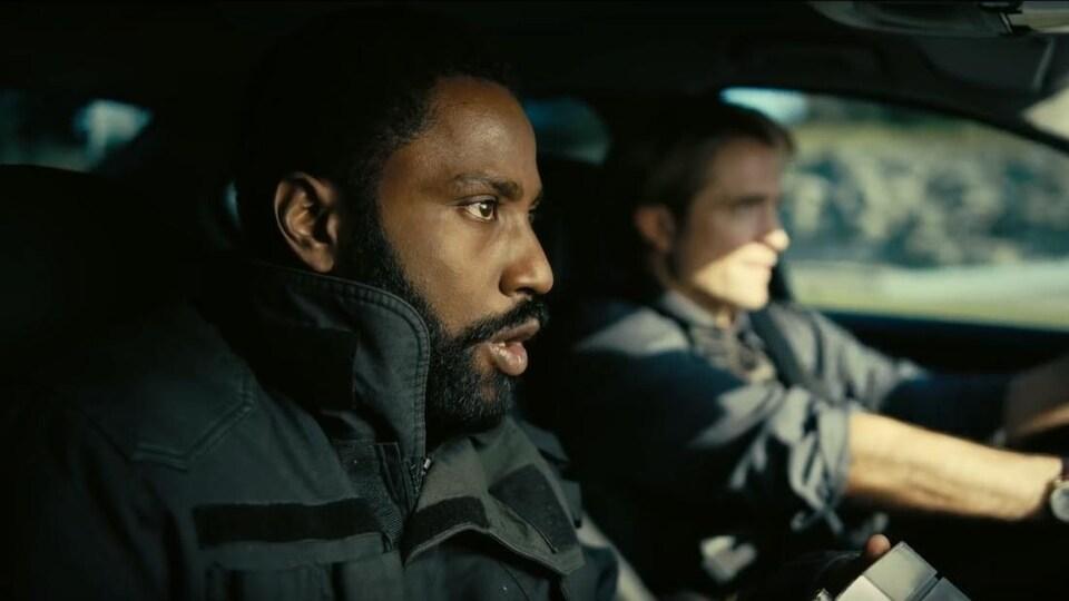 John David Washington et Robert Pattinson sont à l'avant d'une voiture.