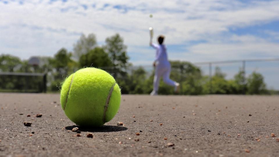 Un joueur de tennis près du filet avec une balle à l'avant-plan.