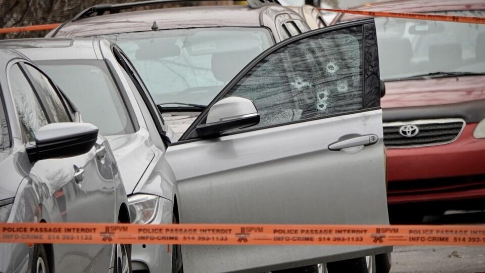 Une voiture dont la fenêtre côté conducteur a été traversée par des balles d'arme à feu.