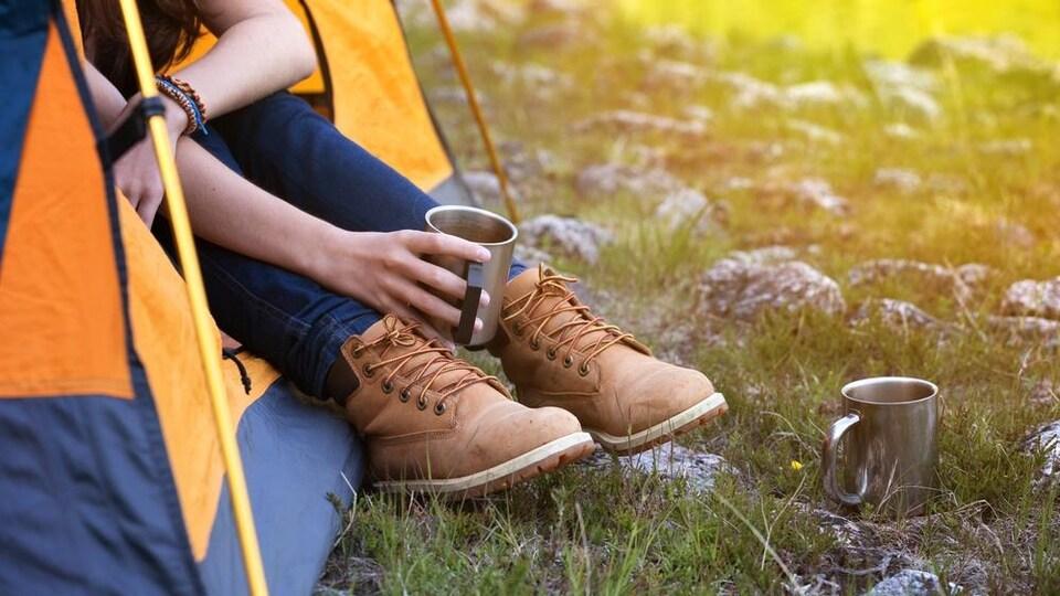 Une campeuse boit un café à l'entrée d'une tente.
