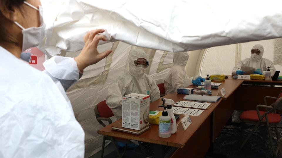 Des médecins masqués sous une tente blanche.